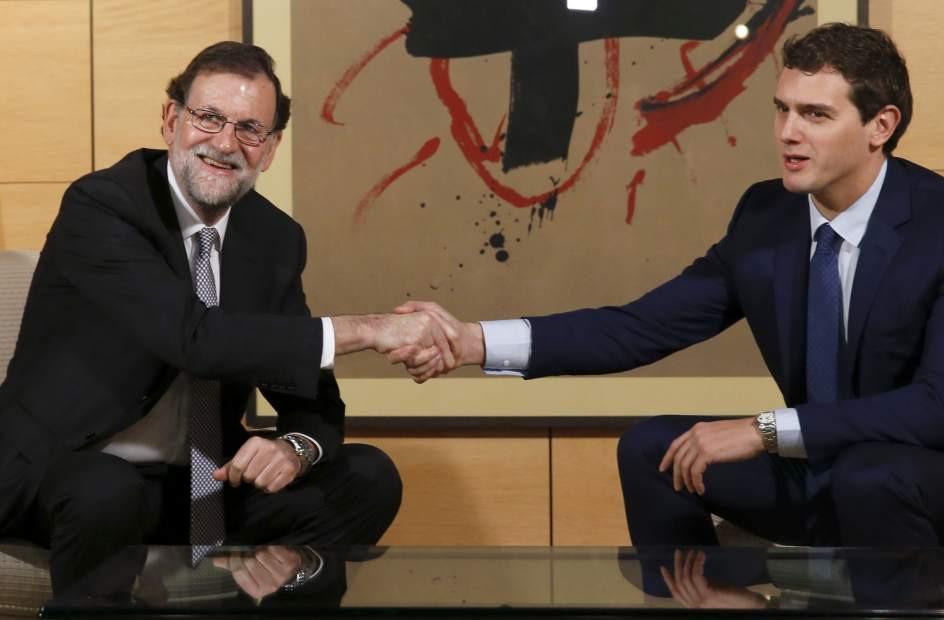 Rajoy estrechando su mano con Rivera