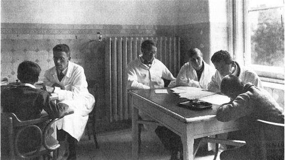 Hans Asperger, a la izquierda, sentado frente a un niu00f1o