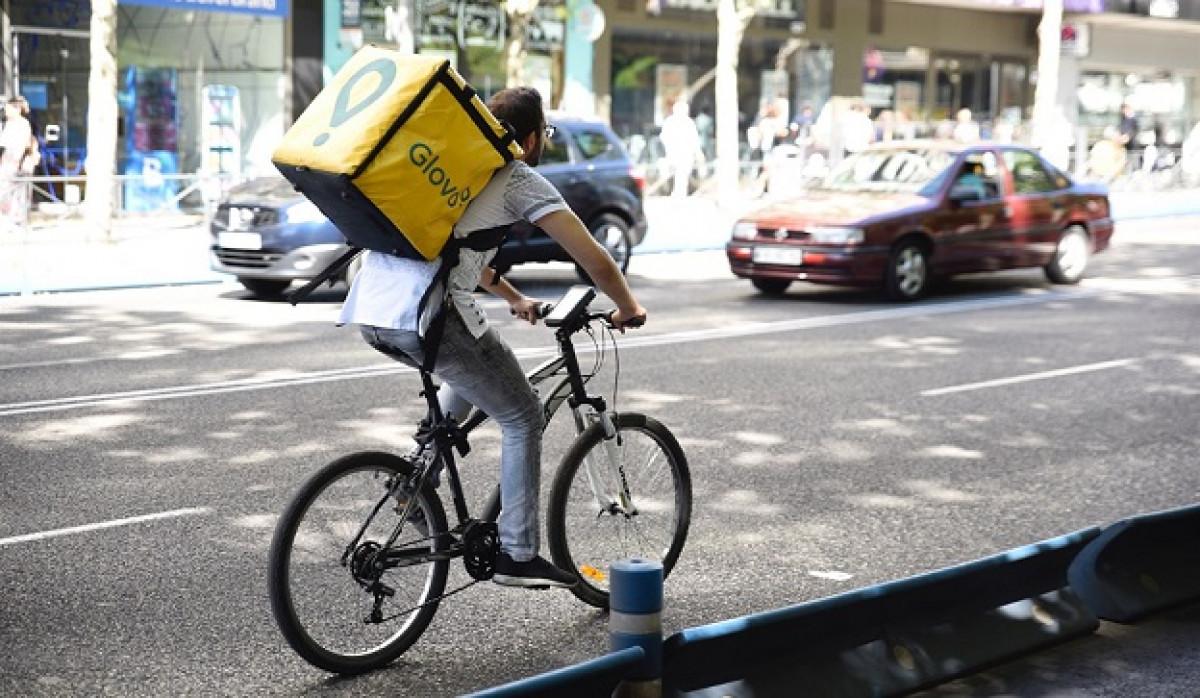 Trabajador de la empresa Glovo montando en bicicleta por Madrid