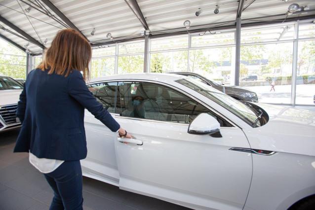 Una mujer abre un coche en un concesionario.