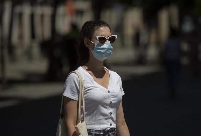 Archivo - Una mujer con mascarilla y gafas de sol  durante el quinto día de la fase 2 en Sevilla (Andalucía, España), a 29 de mayo de 2020.